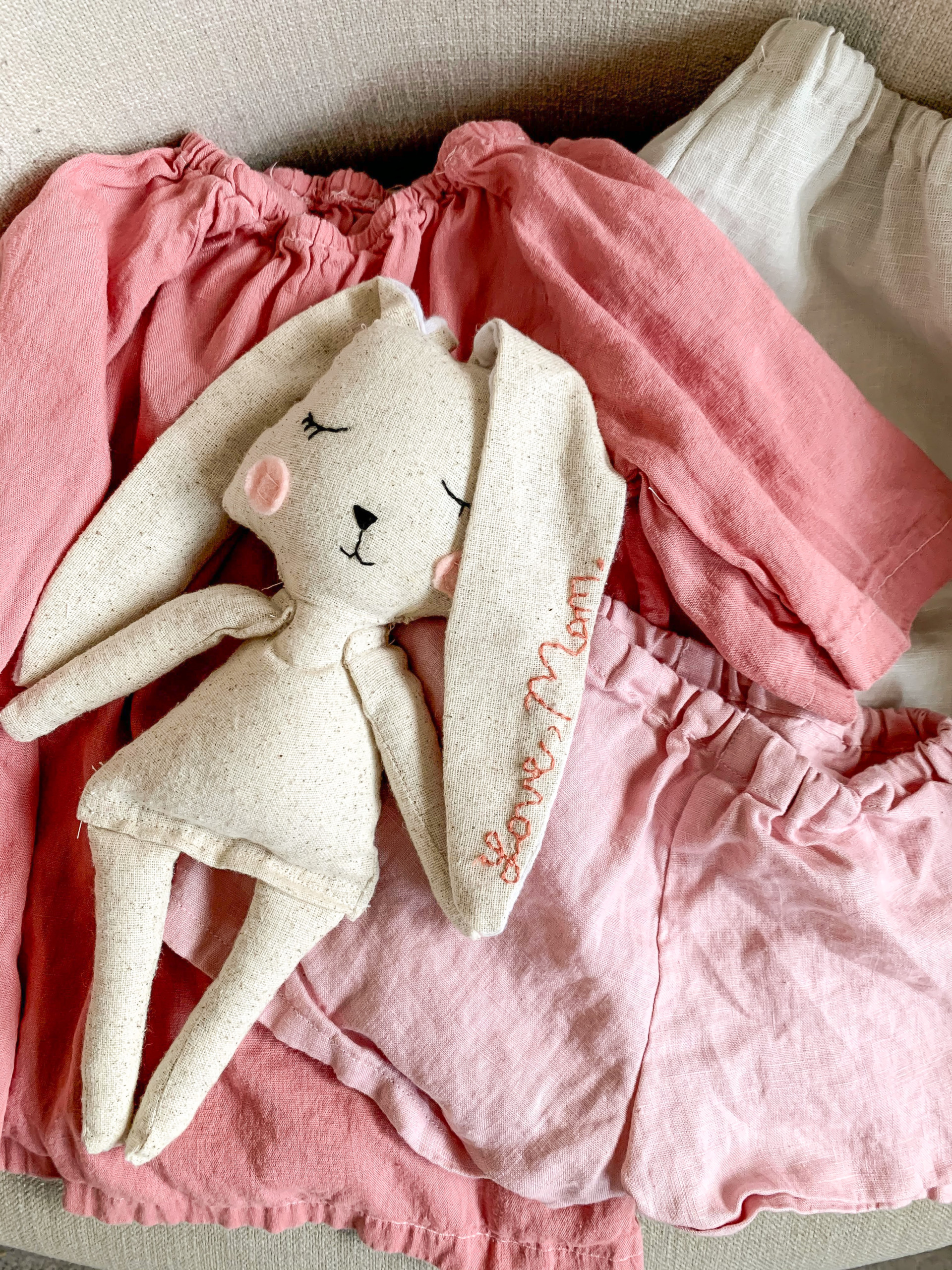 A handmade rabbit doll on top of pink kid's clothes.