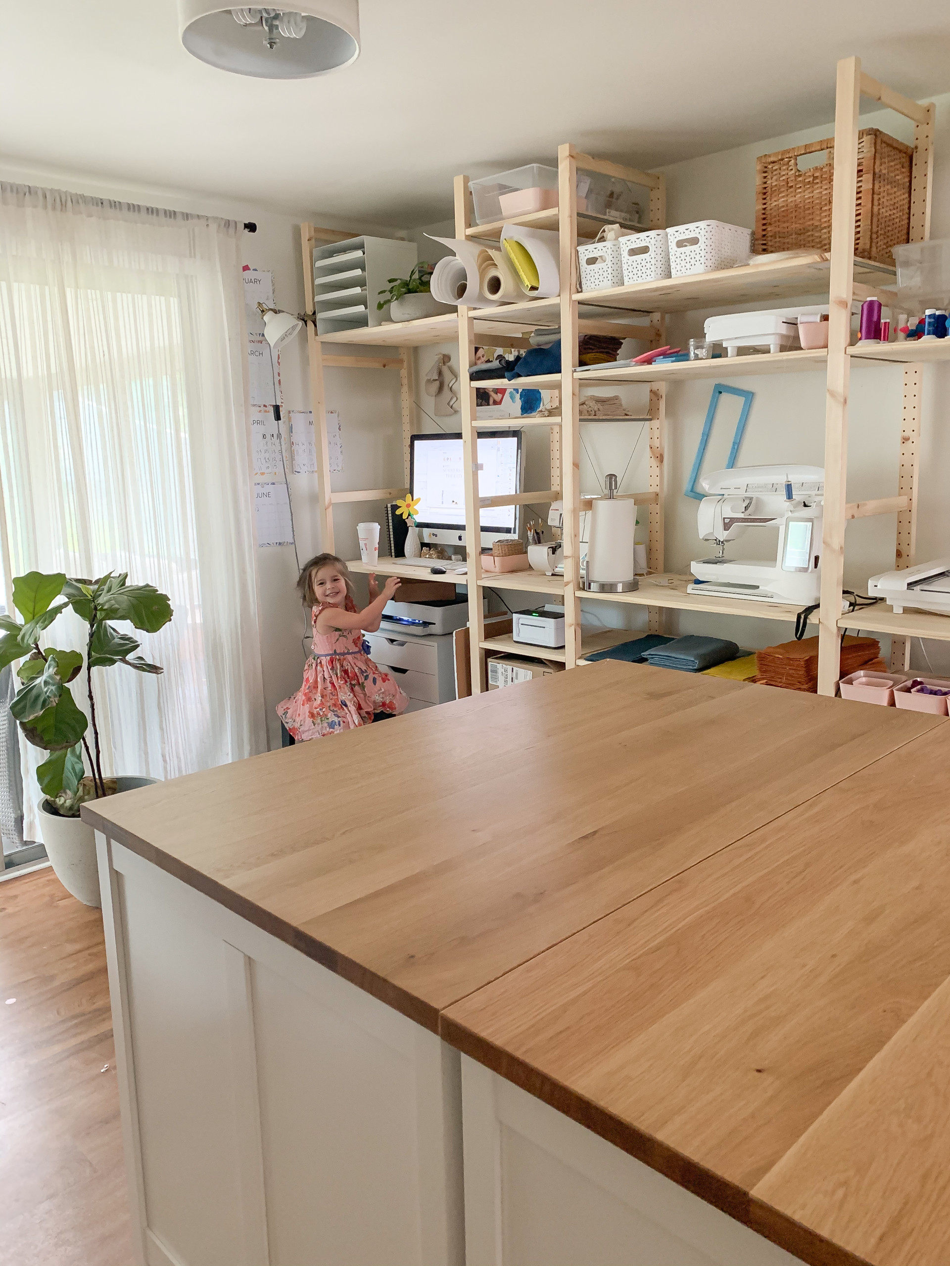 Sarah Cambio's workspace. There's a big wooden island, open wooden shelves filled with materials, and a fiddle leaf fig. Sarah's daughter is wearing pink and sitting by the shelves at a computer.