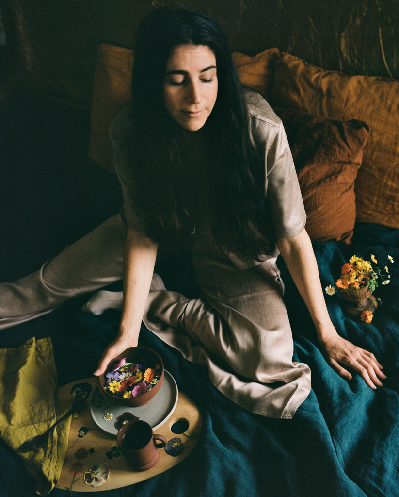Loria sitting on a bed with teal bedding and flowers in a bowl. She's wearing a beige jumpsuit and there's low, moody lighting.