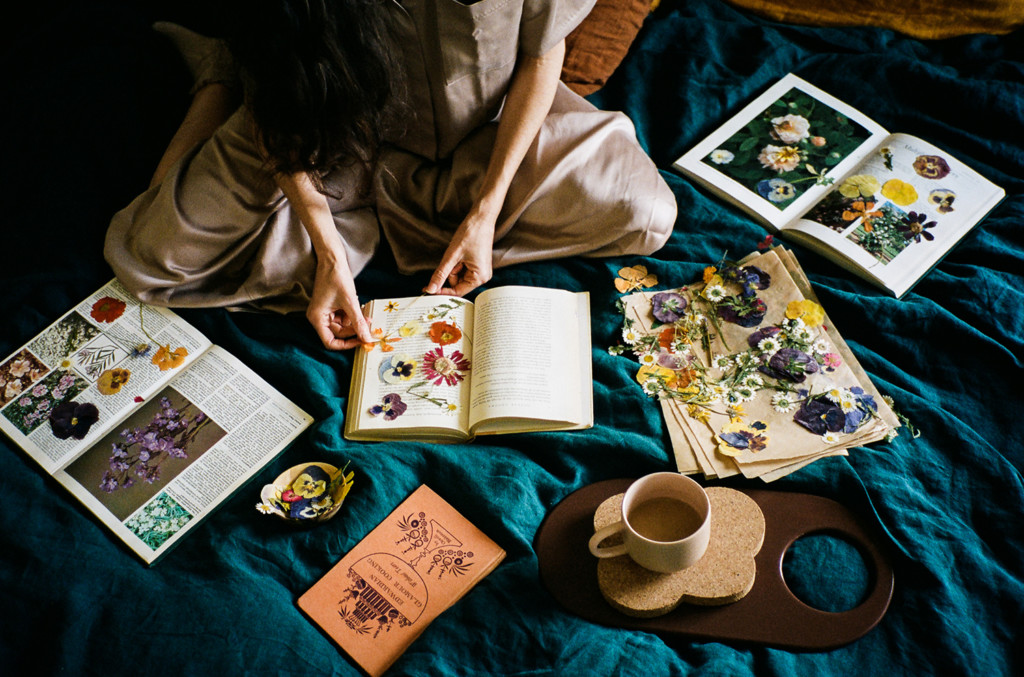 Loria sits cross-legged on a teal blanket surrounded by pressed flowers in books and a cup of tea.