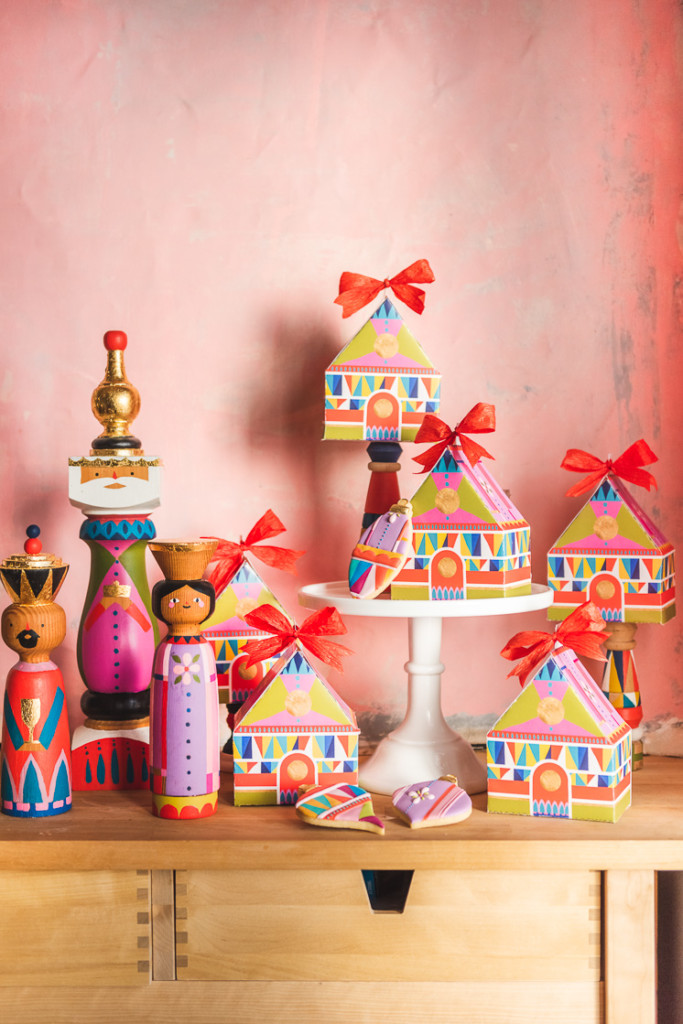 Colorful cookie boxes arranged next to a handpainted midcentury nativity against a pink wall