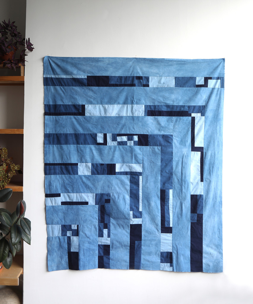 A patchwork blanket made of indigo squares in various shades.
