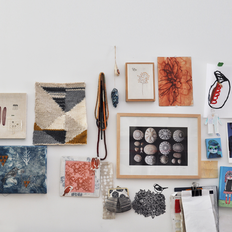 A layout of craft supplies, punch needle projects, and art.