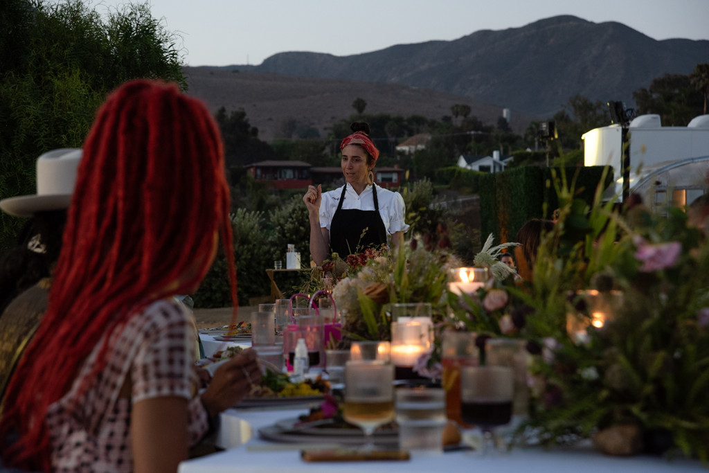 Loria standing at the head of a banquet table full of food and flowers. It is sunset and there are mountains in the background.