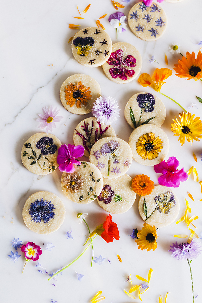 Brightly colored flowers pressed and baked onto sugar cookies on a marble background