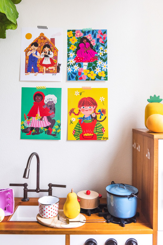 four art prints by Ayang Cempaka hanging above a play kitchen. The prints show hansel and gretel, thumbelina, little red riding hood, and Pippi Longstocking.