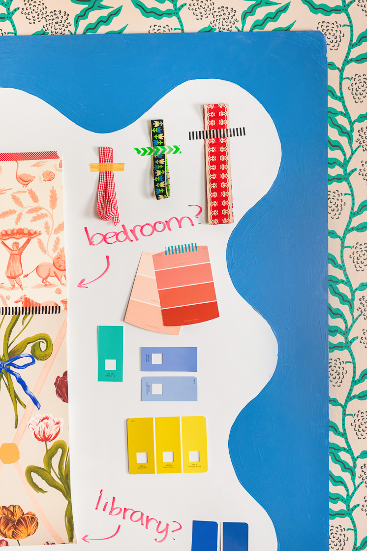 A squiggly-painted whiteboard with paint swatches, ribbons, and other mood board-like objects taped to it. It's on wallpaper with a green botanical design.