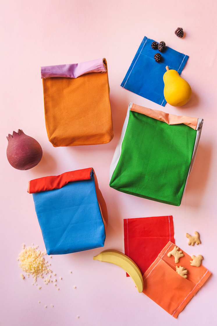 Colorblocked cloth lunch sacks among snacks and wooden fruit on a pink backdrop