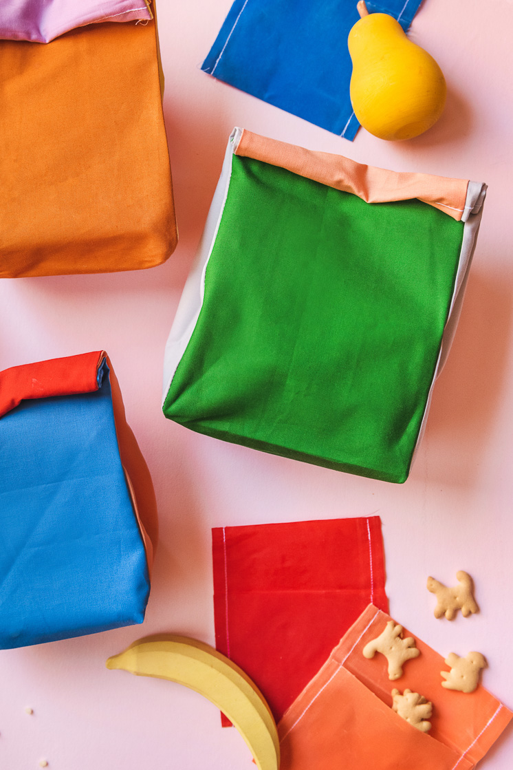 Colorblocked lunch sacks and beeswax snack wraps surrounded by play fruit and animal crackers on a pink background.
