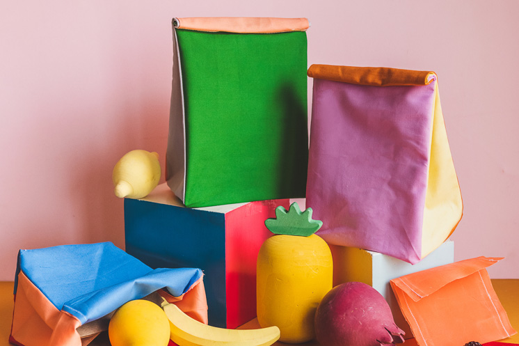 Colorblocked lunch sacks and beeswax snack wraps piled on top of blocks and surrounded by colorful wooden fruit