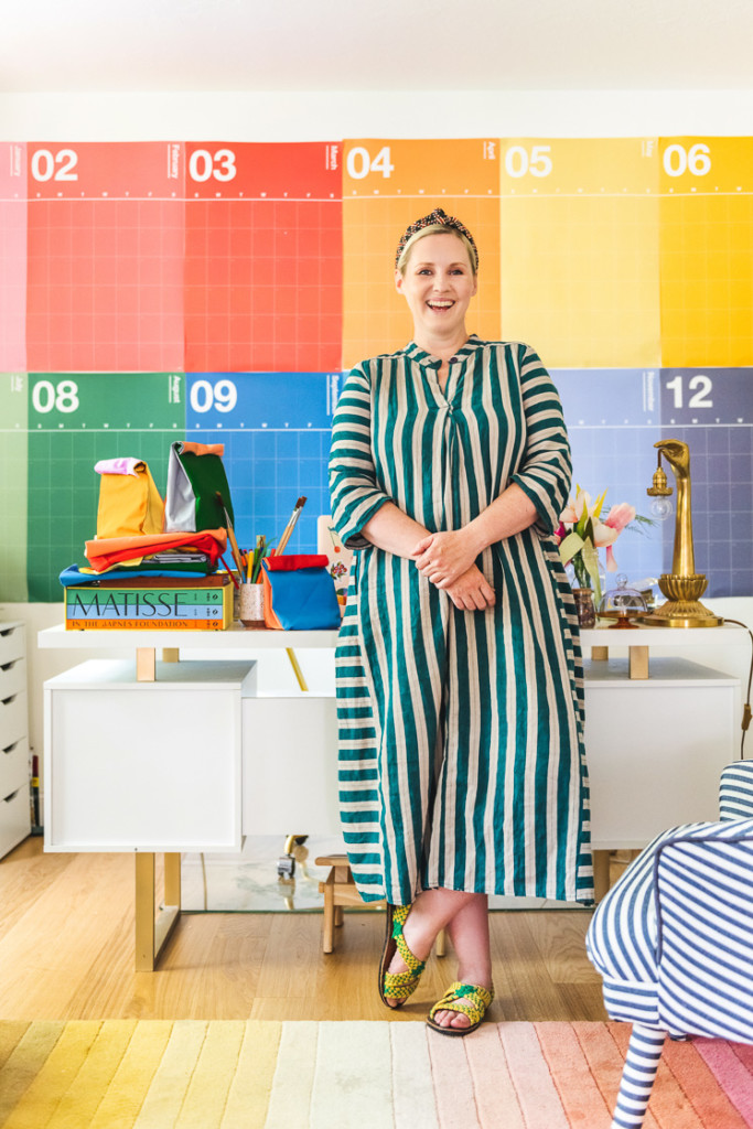 Brittany stands in her rainbow office wearing a green striped dress. Next to her on the desk are some colorblocked reusable lunch sacks.
