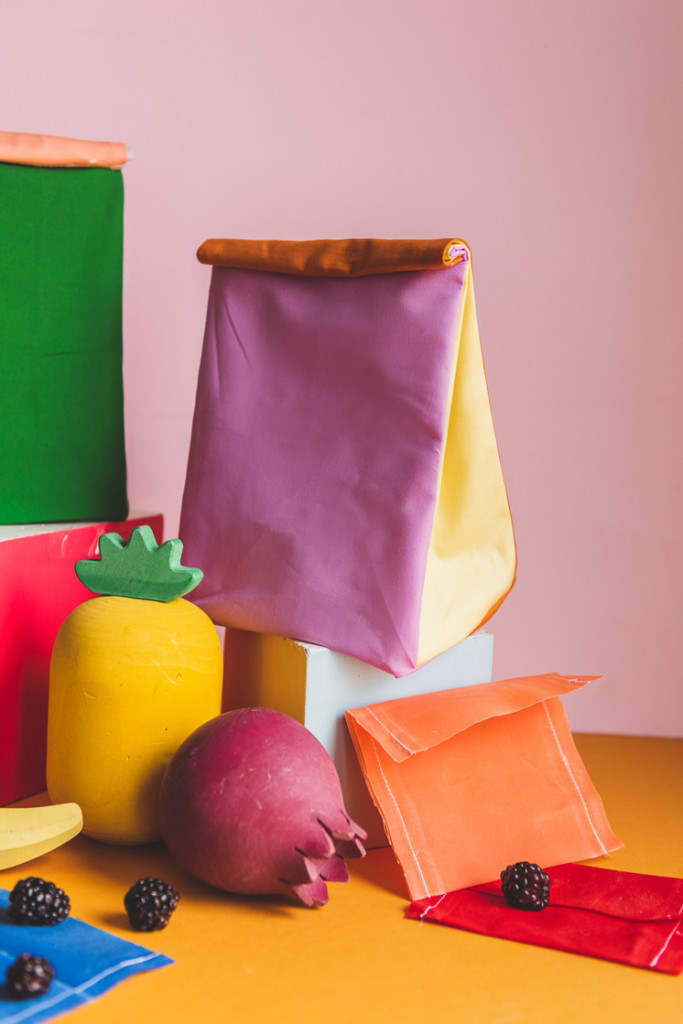 Colorblocked lunch sacks and beeswax snack wraps surrounded by play fruit and blackberries.