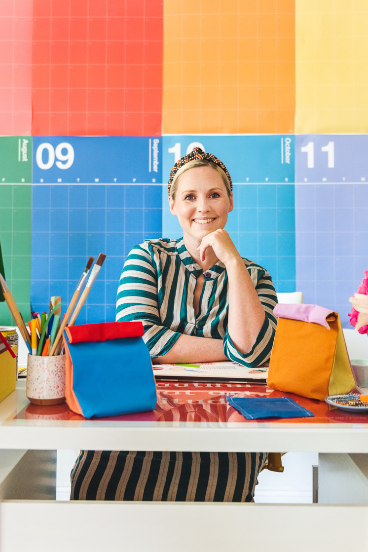 Brittany sits behind her desk surrounded by colorblocked lunch sacks and beeswax snack wraps. THere's a rainbow calendar behind her and she's wearing a striped green dress.