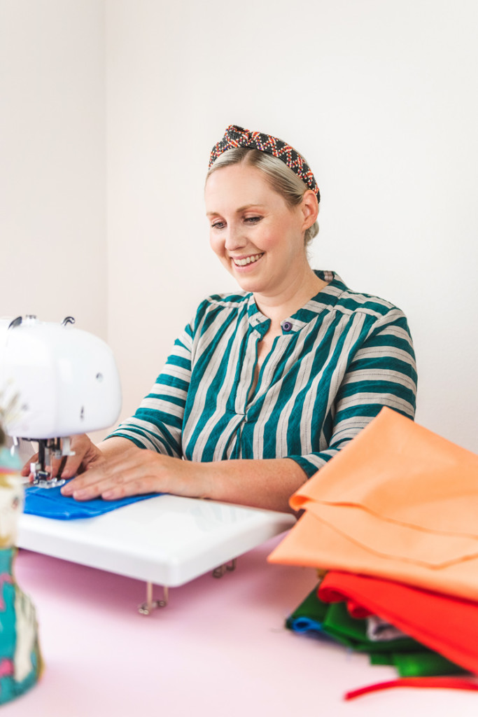 Brittany sits at a sewing machine and makes a beeswax snack wrap. She's wearing a striped green dress and surrounded by colorful, solid fabric.