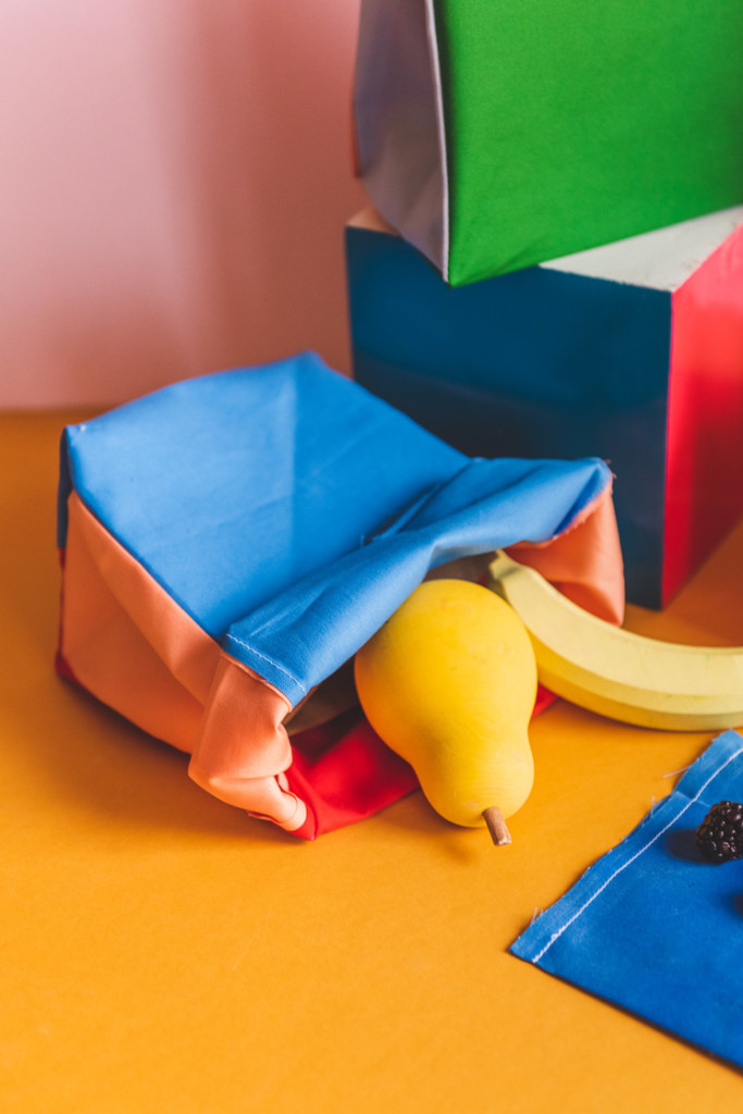 A wooden pear and banana tumble out of a colorblocked lunch sack on a yellow and pink backdrop