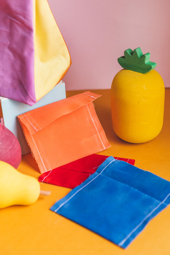 Colorblocked lunch sacks and beeswax snack wraps surrounded by play fruit.