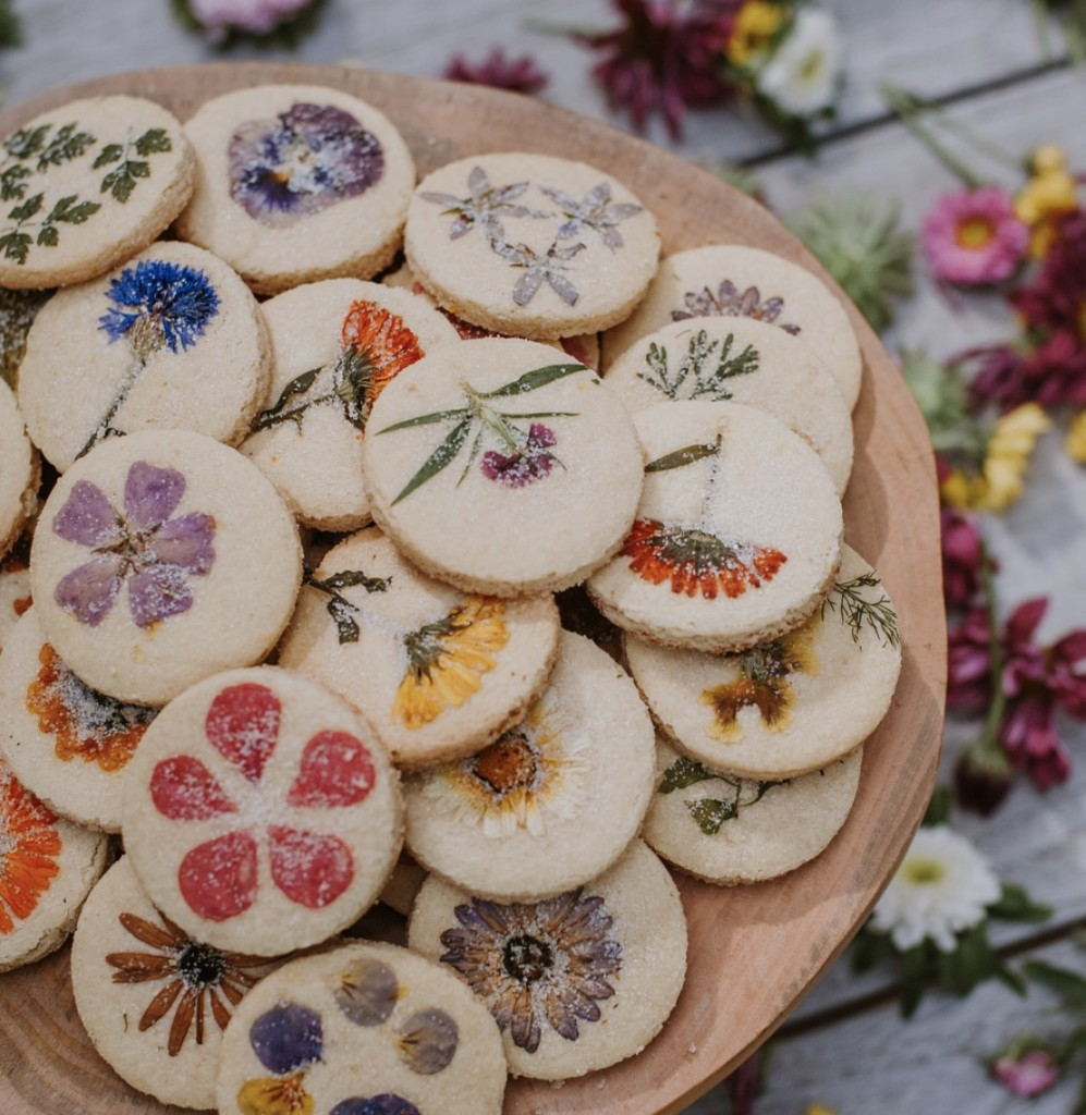 A plate of baked floral shortbread stacked up. In the background there are lots of flowers scattered.