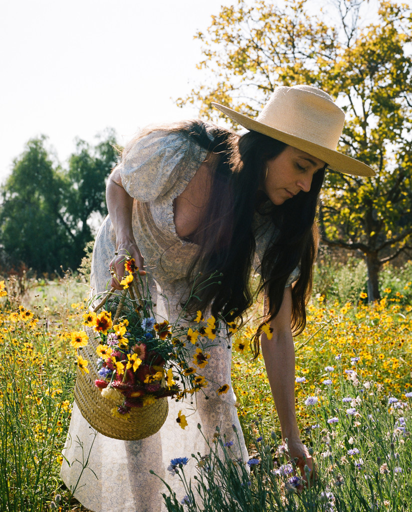 Loria bends down to pick wildflowers in a meadow. She's wearing a white dress and a straw hat.