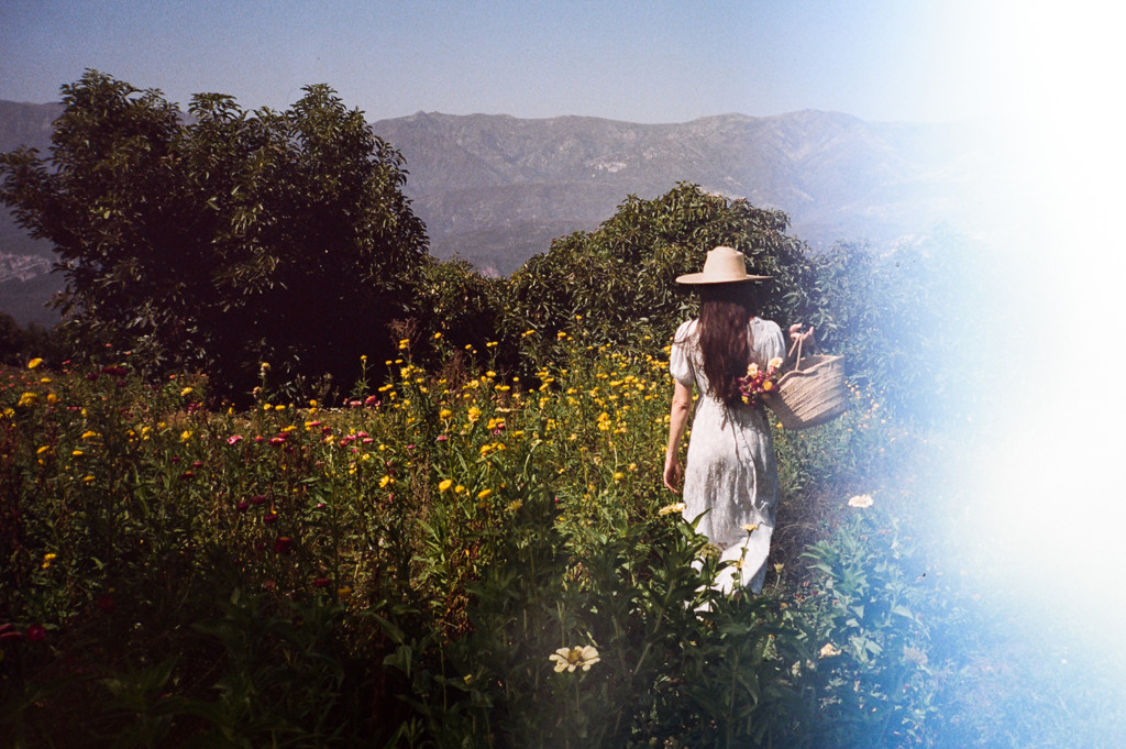 A film photograph of Loria walking away from the camera through a field of wildflowers. She's wearing a white dress and a straw hat and there are trees and mountains in the background.