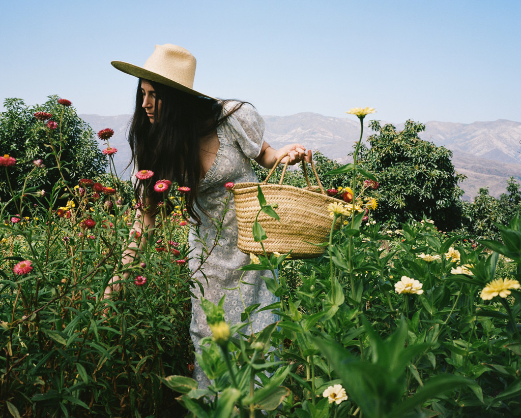 Loria stands in a field of zinnias wearing a white dress and a straw hat. She's holding a basket full of flowers.