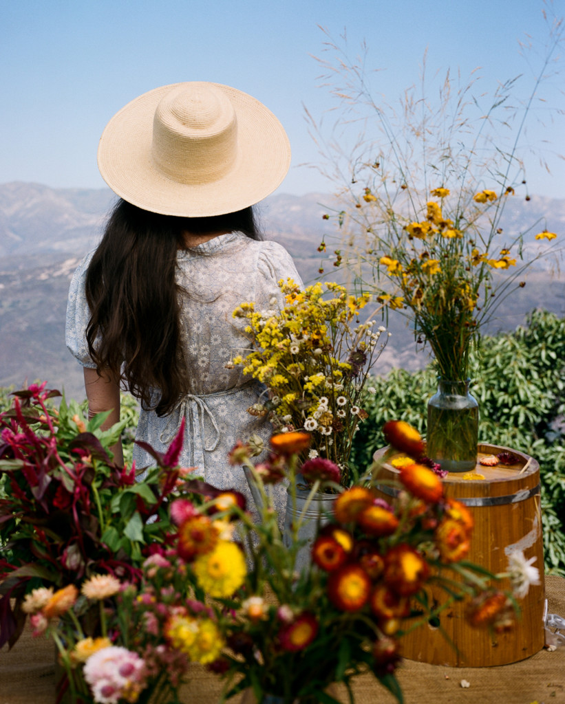 Loria stands with her back to the camera. She's surrounded by fresh cut flowers and she's wearing a straw hat, and there are misty mountains in the background.