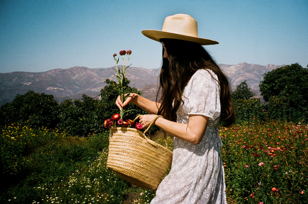 Loria walking through a meadow of flowers wearing a white dress and a straw sun hat. She's holding a basket of flowers and the sky is blue.