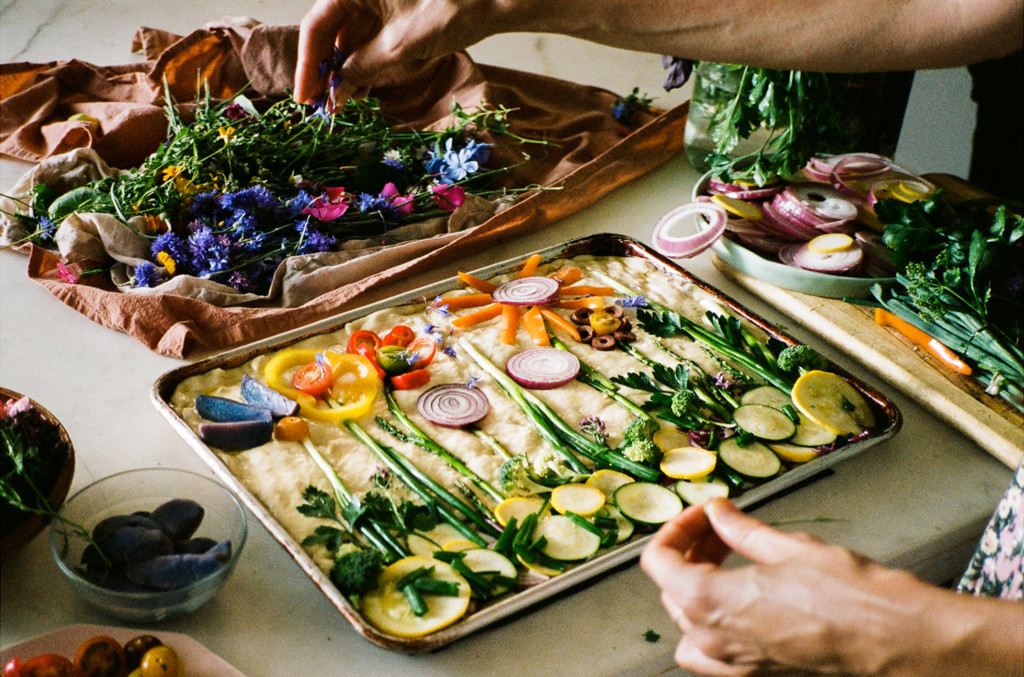 Loria decorating a pan of focaccia with flowers and vegetables. She's shaped them into a floral scene.