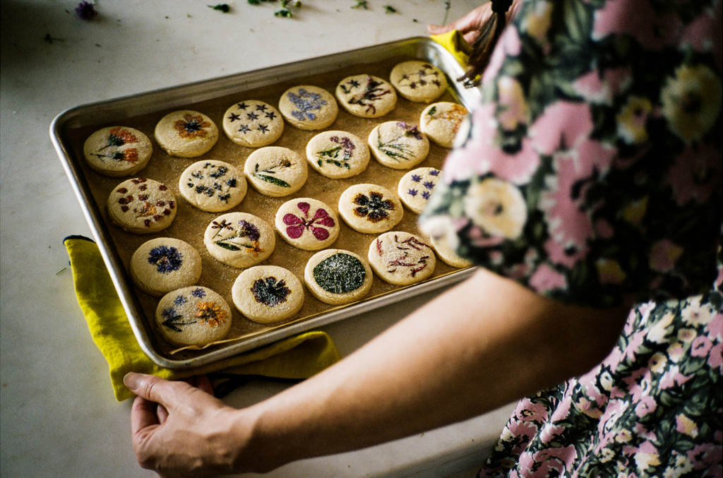 Horizontal photo of Loria wearing a floral dress and holding a tray of baked cookies. Flowers are pressed onto the top of each one.