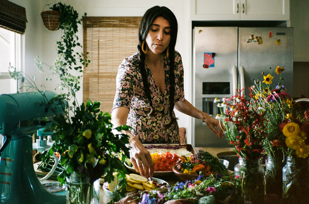 Loria is wearing a floral dress and standing in a kitchen surrounded by colorful produce.