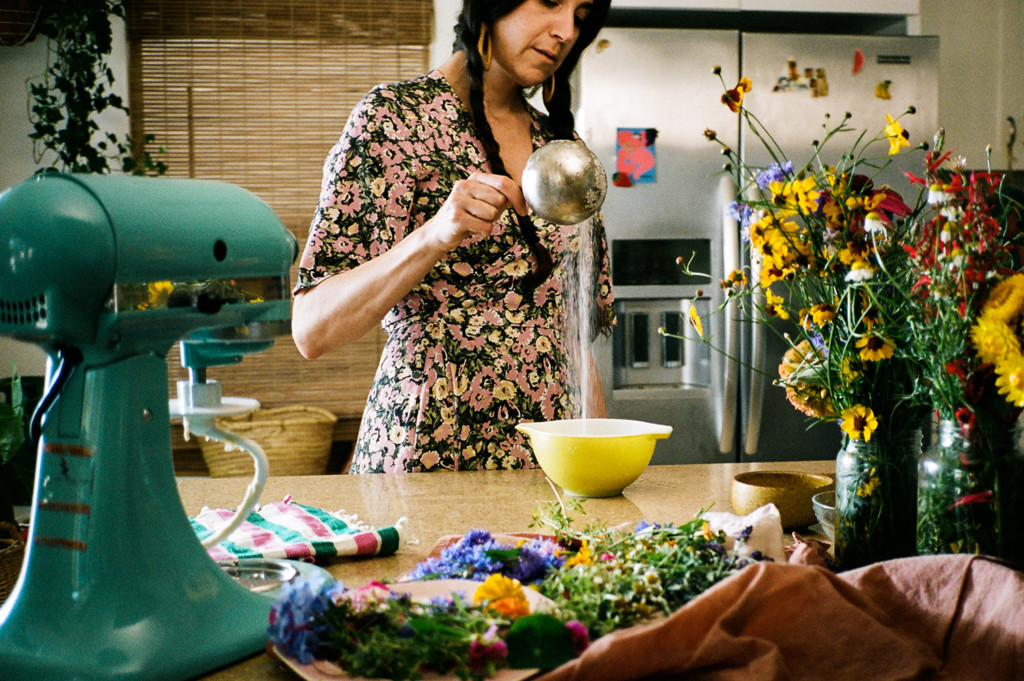 Horizontal photo of Loria measuring sugar into a yellow mixing bowl. She's in a kitchen and surrounded by flowers and a turquoise kitchenade mixer