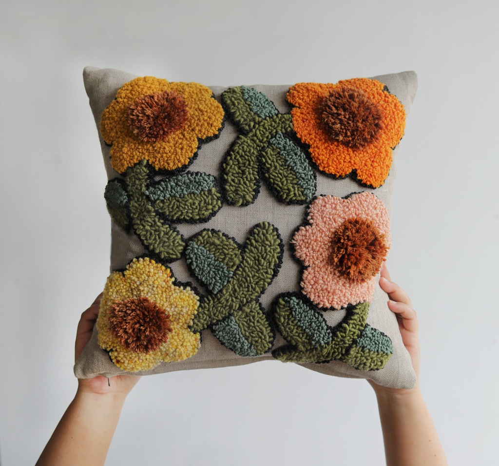 floral punch needle pillow in warm oranges, pinks, yellows, and greens.