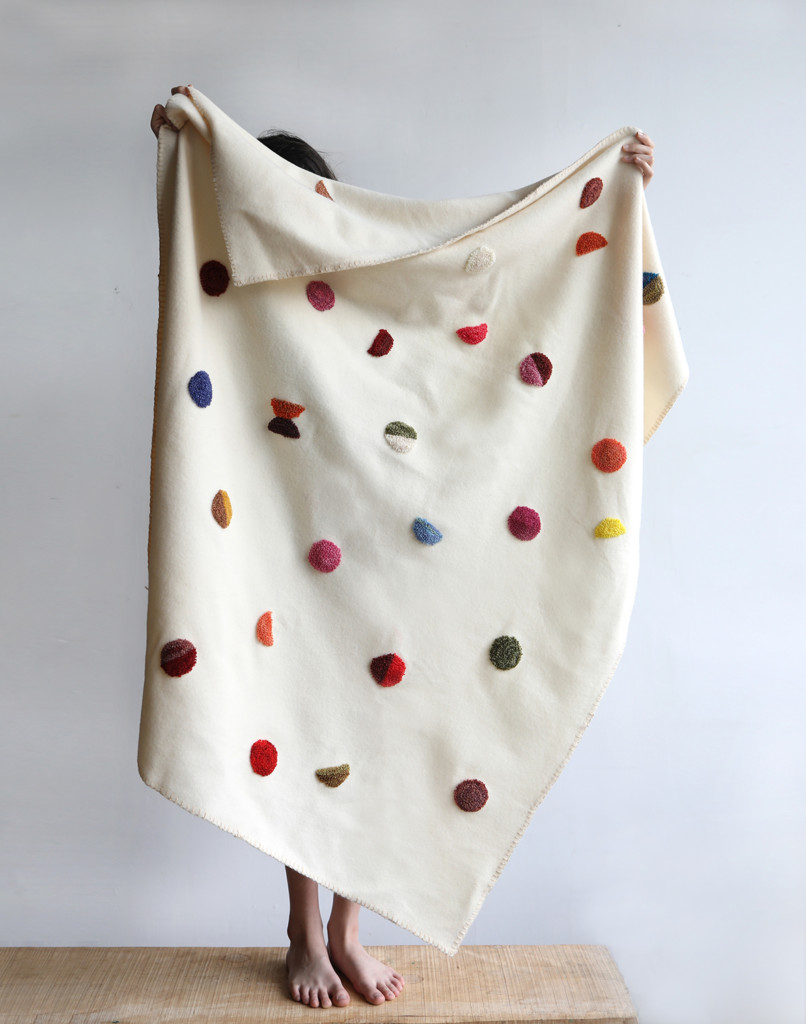 Someone stands on a bench holding a white punch needle blanket above their head. The punch needled parts are in lots of colors and look like confetti dots sprinkled throughout the blanket's surface.