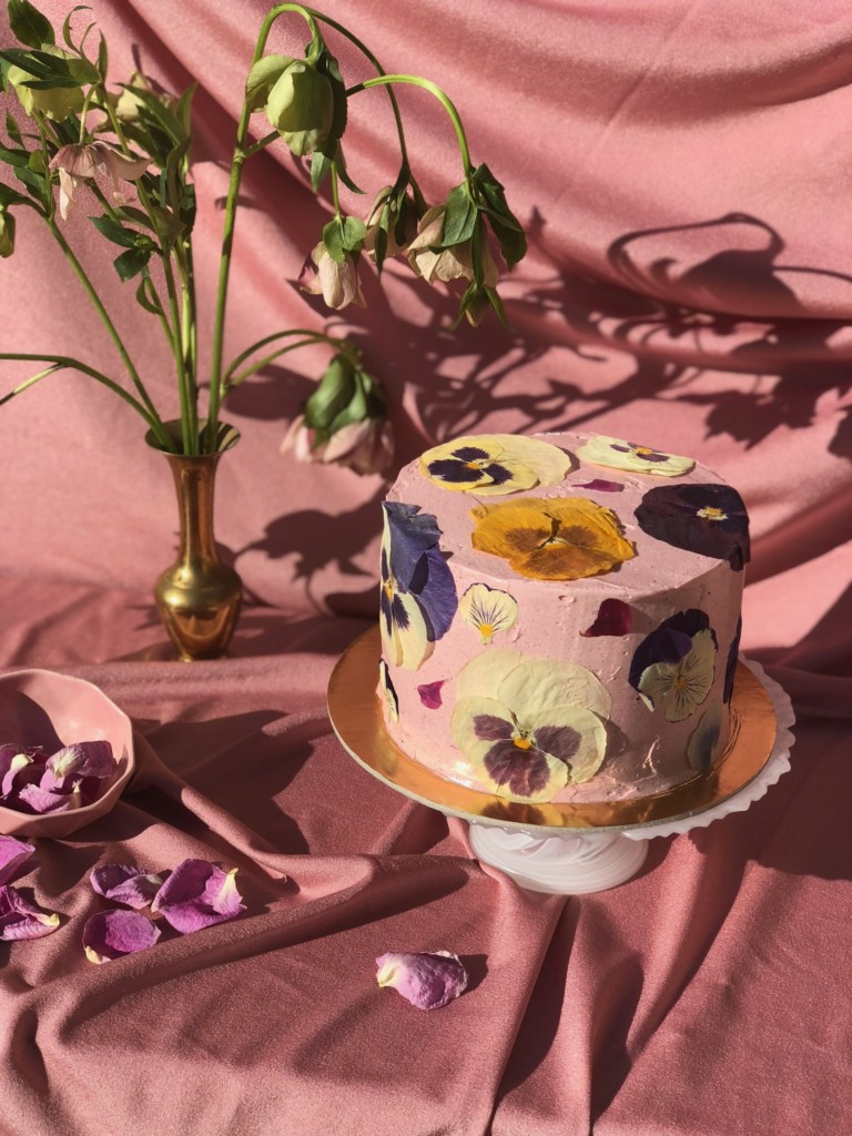 cake frosted with blush pink frosting with purple, yellow, and white pansies pressed onto it. It's styled in a pink draping fabric with a vase of flowers.