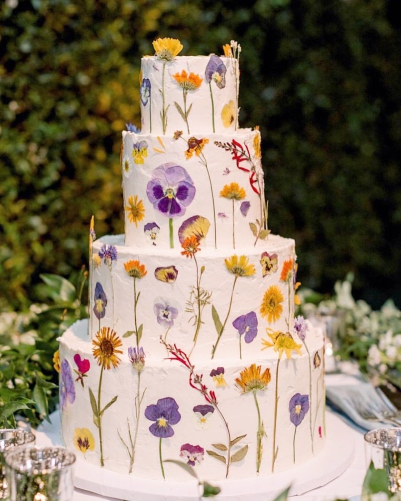 Tall wedding cake frosted with white frosting and purple and yellow flowers