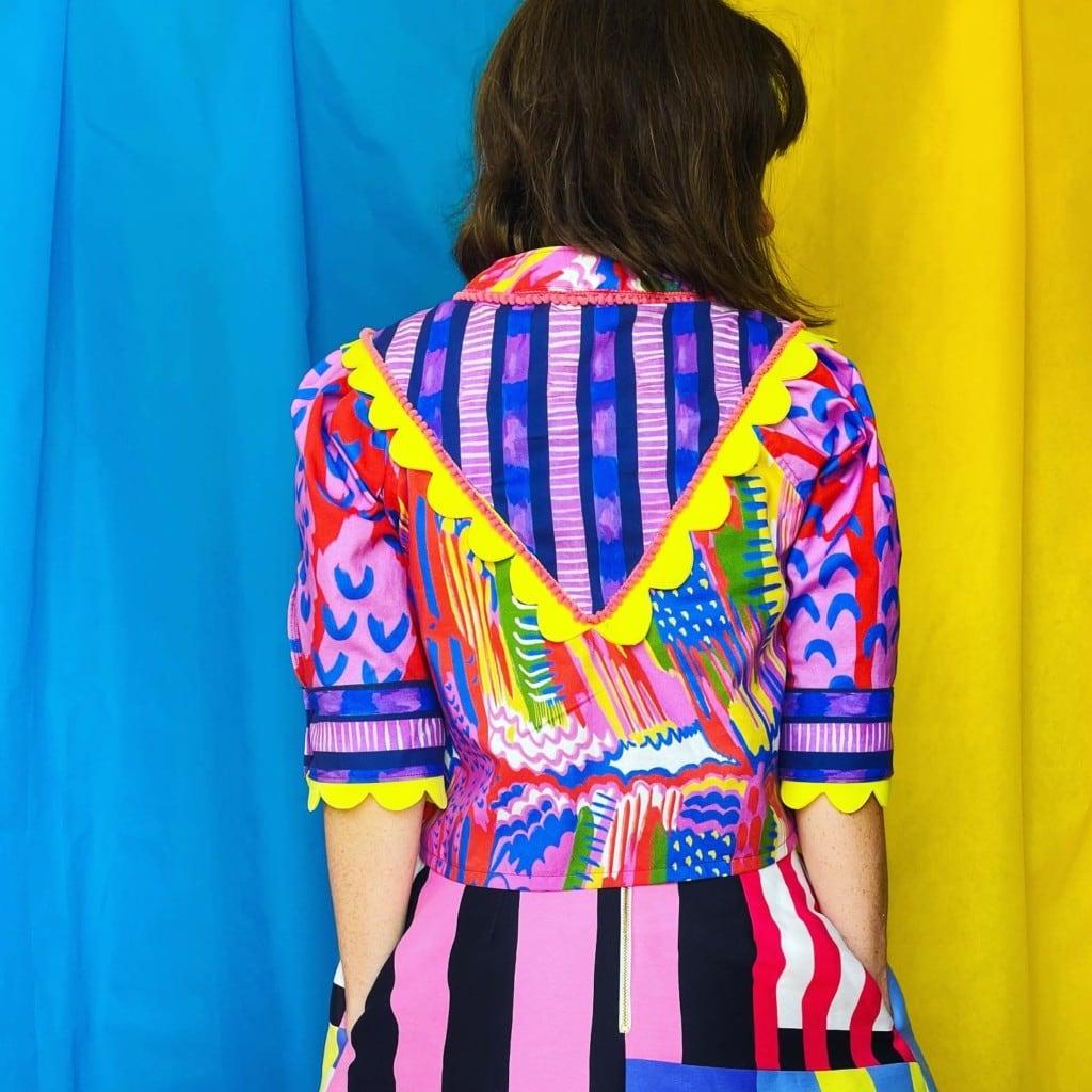 Katie Kortman modeling a vibrant dress she's designed.