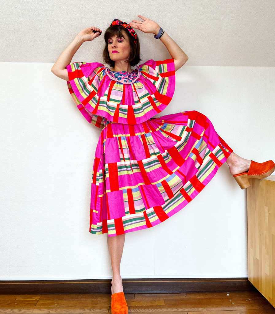 Katie wears a pink, red, green, and cream dress with red clogs. She's standing with her arms raised to demonstrate the dress bodice and sleeve flowiness.