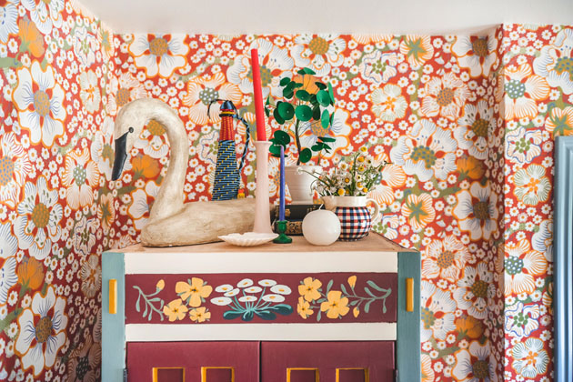 the top of a painted armoire against a red floral wallpaper background. On top of the armoire is a sculptural duck, a candle and candlestick, a paper money plant, and some cute odds and ends.