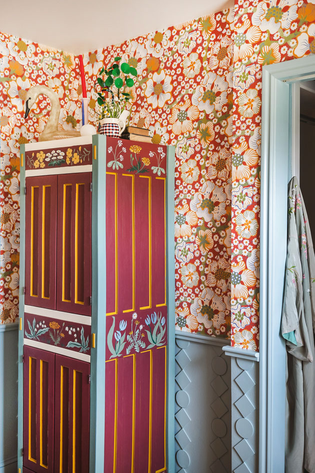 Interior shot of a custom painted cupboard and blue DIY wainscoting in a red floral bathroom.