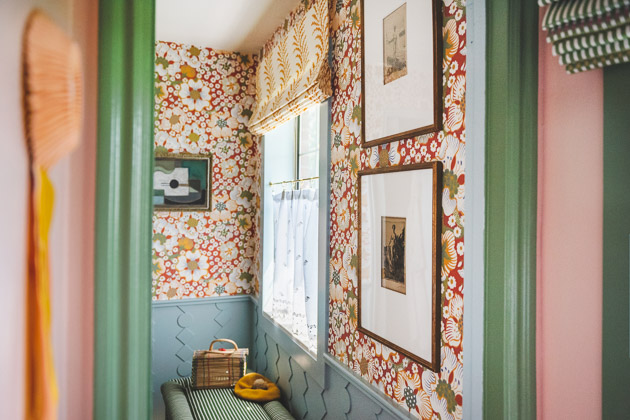 Interior shot of the red wallpapered bathroom from inside a pink and green painted closet.
