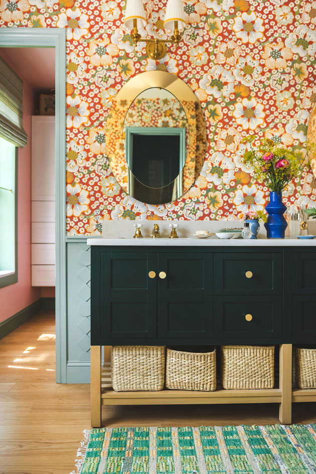 Interior shot of a green bathroom vanity with wicker baskets under it, a green rug, flowers in vases on top, and a mirror hanging above it. There's red floral wallpaper and blue painted trim.