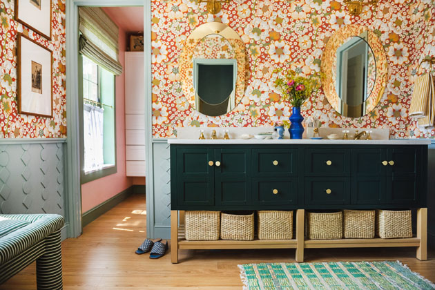 Horizontal interior shot of a bathroom with red floral wallpaper, a green vanity with brass knobs, and blue diy wainscoting.