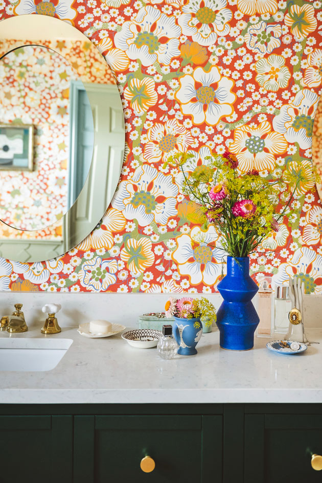 Interior shot of a bathroom with a dark emerald green vanity and red floral wallpaper. There are flowers on the vanity countertop,and brass knobs and fixtures.
