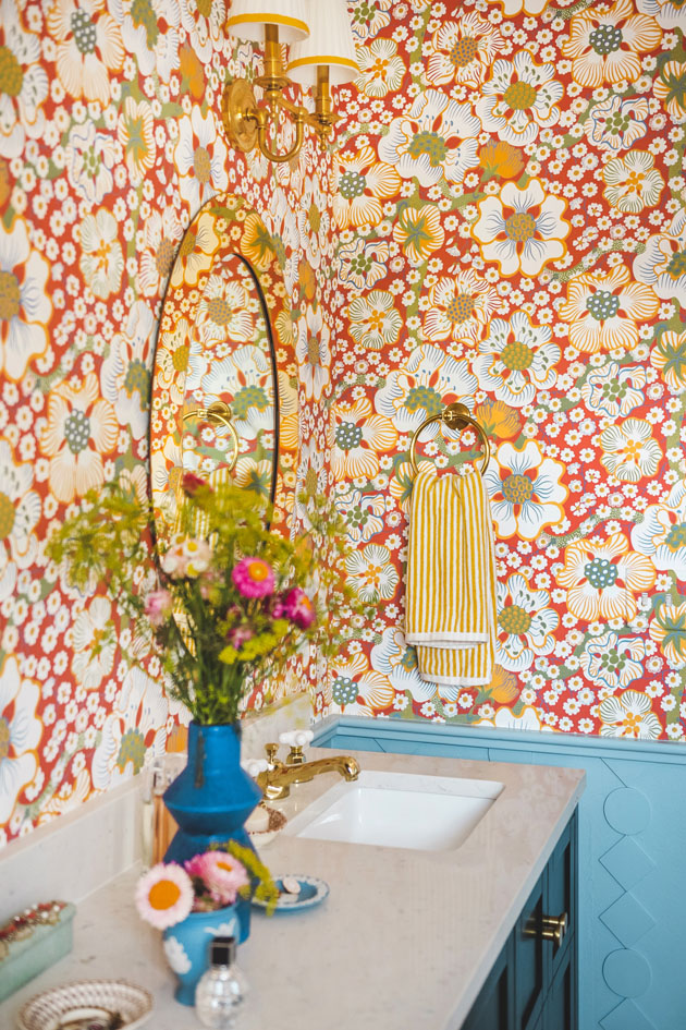Interior shot of a bathroom with a dark emerald green vanity and red floral wallpaper. There are flowers on the vanity countertop, brass knobs and fixtures, and a blue custom wainscoting.