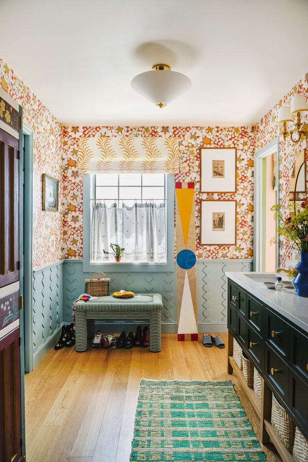 Interior shot of a bathroom. There's red floral wallpaper and framed art prints on the walls, blue textured wainscoting and trim, wooden floors, yellow window treatments, and eclectic styling.