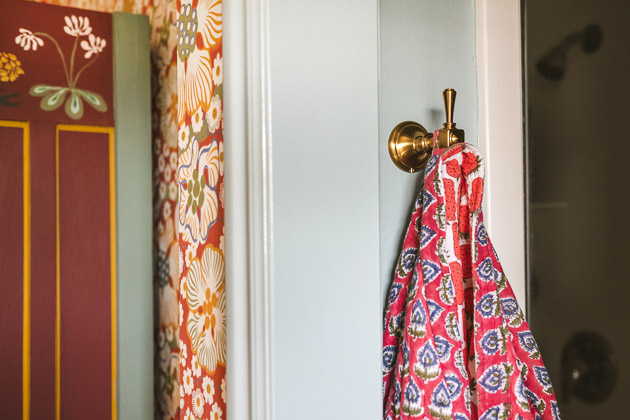 A pink and blue batik-patterned bathrobe hanging on a brushed gold hook in a bathroom. You can see a doorway and a red, floral bathroom on the side of the image.
