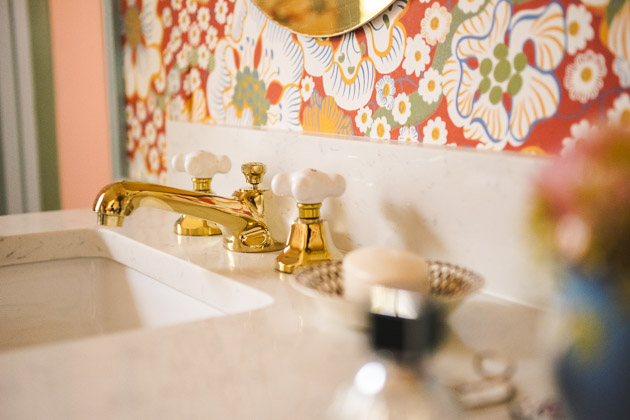 A brass faucet with white ceramic knobs on a white marble countertop. The wallpaper behind it is red and floral.