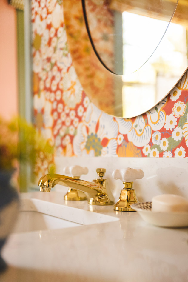Brushed brass faucets on a marble countertop with a periwinkle vase of flowers. There's red floral wallpaper in the background.