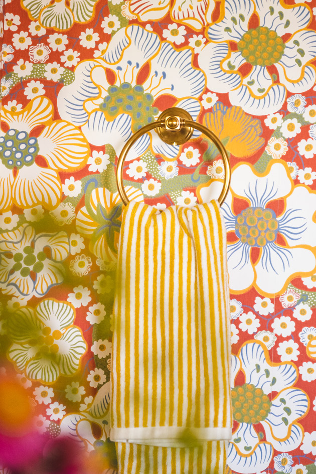 A yellow striped hand towel hangs on a brass ring on the wall. The out-of-focus silhouette of flowers in a vase shades some of the image.