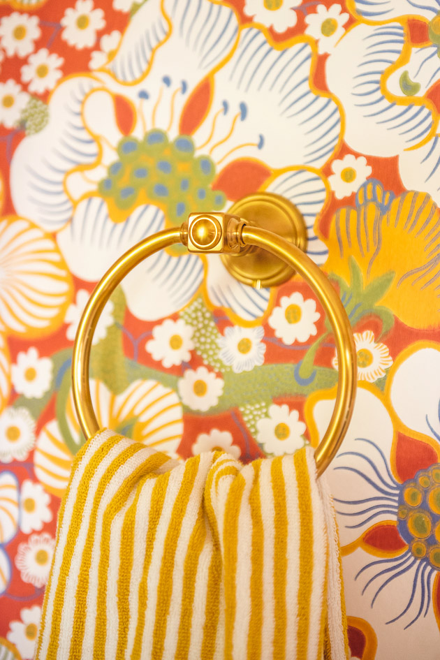 Close up of a brass towel ring. A yellow and white striped hand towel hangs from it, and there's red floral wallpaper in the back.