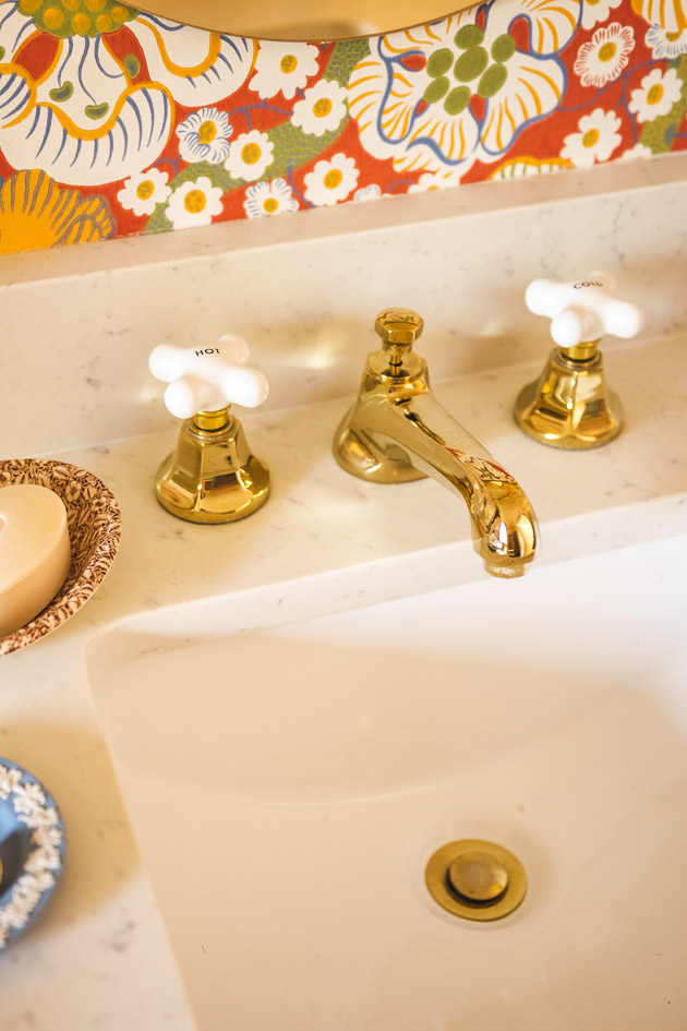 gold faucet on a marble countertop. The handles are ceramic.